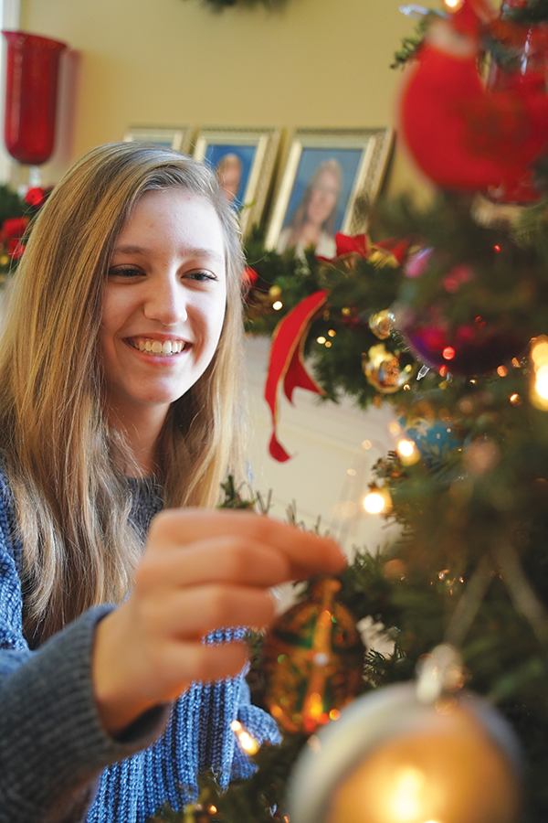 Senior Alana Blumberg hangs an ornament on her family's Christmas tree. She said this is a family tradition.