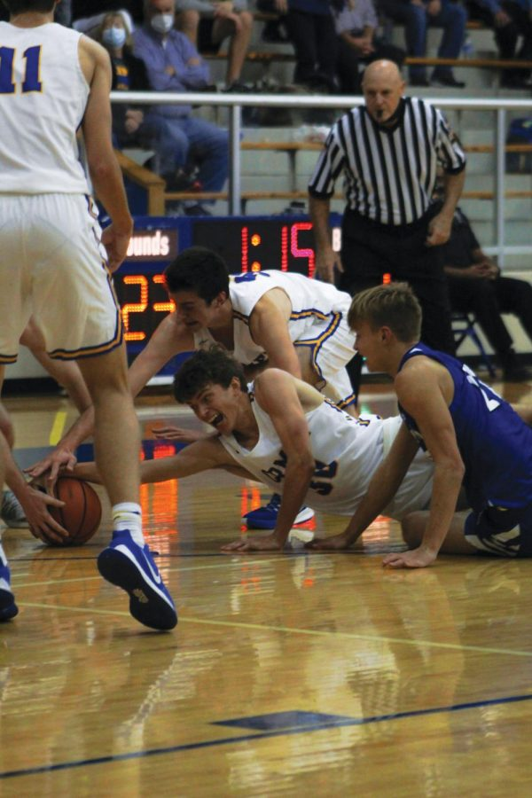 HIGH HOPES: Wil Leary, varsity basketball player and senior, attempts to take a ball during a basketball game on Nov.24. According to Leary, basketball games and practices have been constantly changing since the beginning of the school year. However, despite changes and new safety procedures, Leary said he is still excited to play for the new season and hopes to win many games.