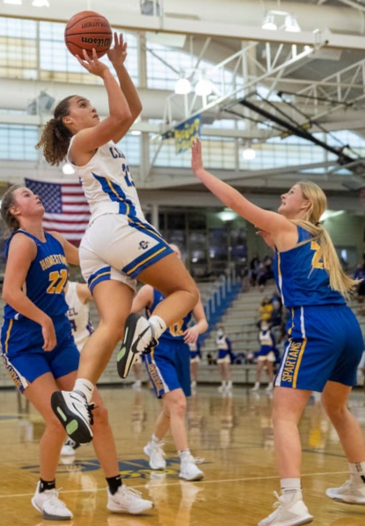 Caption: Riley Pennington, varsity basketball player and senior, plays in a game against Homestead High School. Pennington said there were only three games remaining in the season. (Submitted Photo: Riley Pennington)