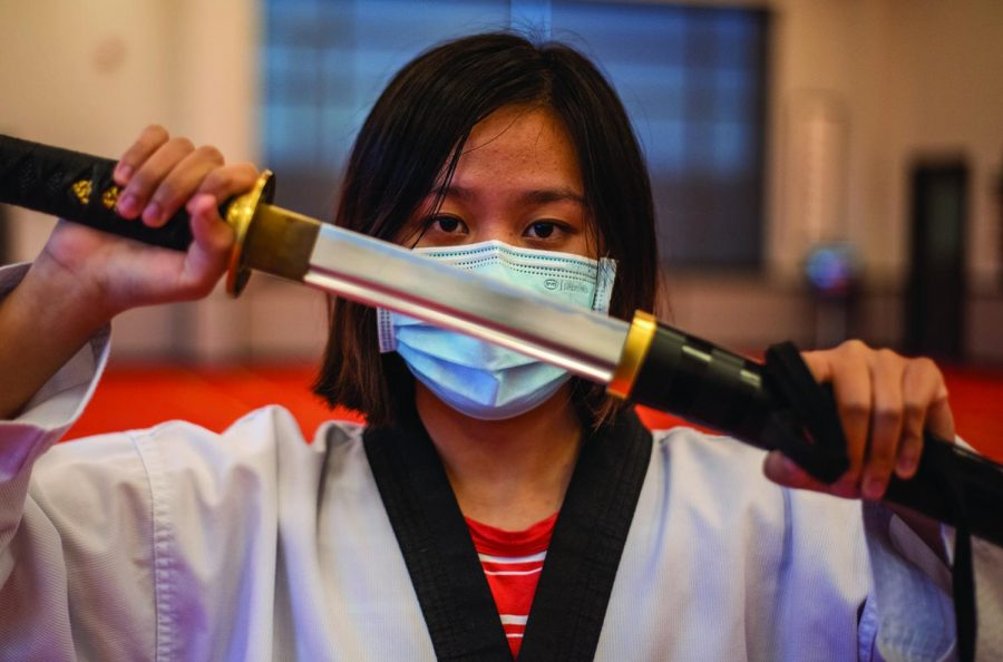 Sophomore Avery Guo poses with a sword in her dojang. Guo said the instructors at her dojang have taught her how to properly defend herself both with and without weaponry.