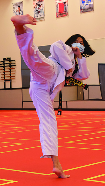 Sophomore Avery Guo practices a kick in her dojang. Guo said everyone should practice a martial art at some point in their life. Martial arts instructor Kasi Young said she teaches students of all ages.