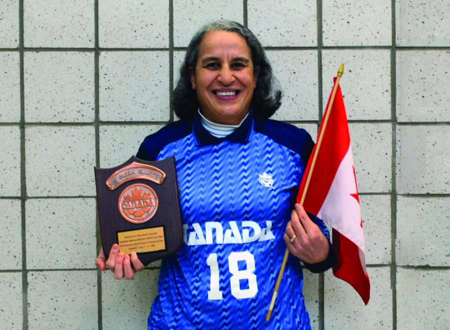 Staff member Carla Baker poses with her Canadian National Women's World Cup team plaque, jersey, and Canadian flag. She played in the 25th Anniversary Tournament against France, Italy, and the US.