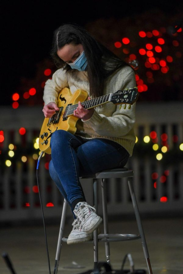Junior Bianca Templeton plays an electric guitar during Hope for the Holidays at the Carmel Gazebo on Dec. 9. The CHS Cabinet organized the event to raise money for kids at the Riley Children's Hospital. The show, divided into eight holiday performances, can be viewed on the Carmel Dance Marathon's Instagram and Twitter.