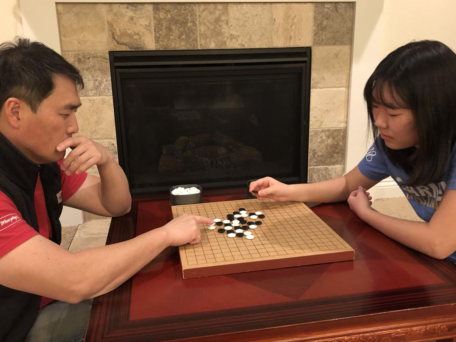 Senior Lauren Lee plays a Korean Board game called baduk with her father Kristian Lee. She said it is similar to the Chinese game Go, where the objective is to have the players cover as much of the board. as possible.