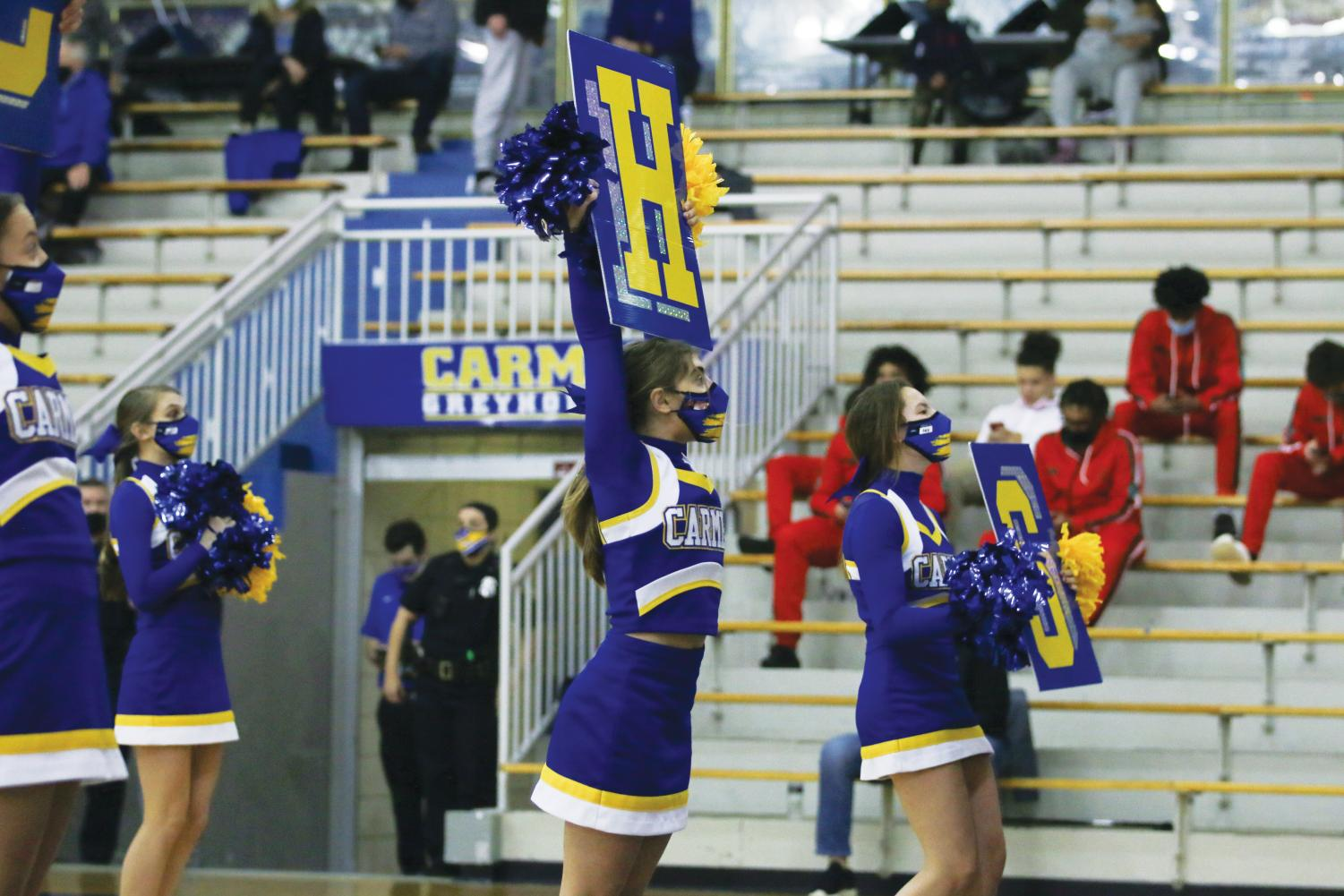 CHEER ON: Cheerleaders perform while holding signs. According to Brooke Kibler, head coach of fall cheerleading, safety precautions contribute to successful  seasons and more moral support.