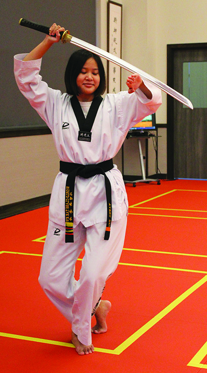 Sophomore Avery Guo practices her sword technique in her dojang. Guo said it is important for women to know how to defend themselves, something taekwondo has taught her.