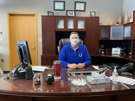 Principal Tom Harmas wears his mask to comply with COVID-19 guidelines while sitting at his desk. He said that administration is redeveloping the school's Response to Intervention model to best meet student needs during the pandemic.