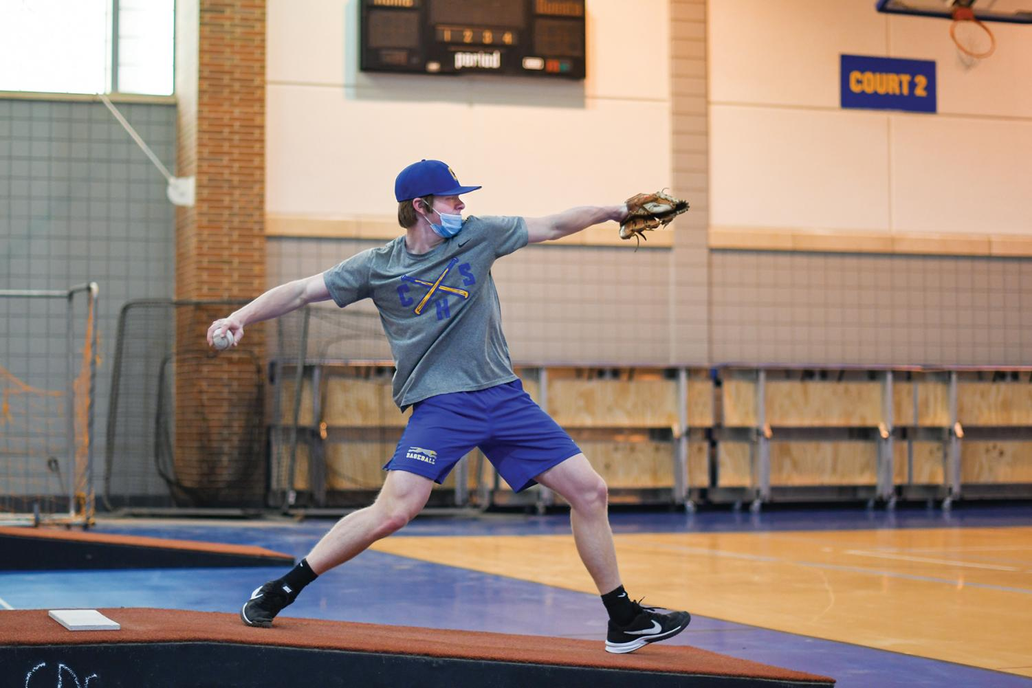 PITCH PERFECT:   Daniel Cunningham, varsity baseball player and junior, practices pitching indoors. Cunningham said practices have been more difficult during the pandemic due to more baseball fields and training facilities being closed.