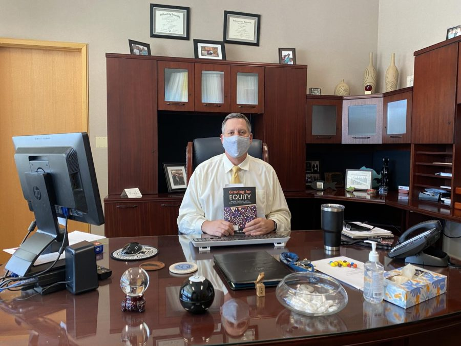 Principal Tom Harmas sits at his desk, holding the book Grading for Equity. He said that this book has helped him gain a better understanding of how grades should reflect student growth. He said that administration has been working throughout this year to make changes to the grading system so that grades are a true representation of a student's learning and engagement throughout the semester.