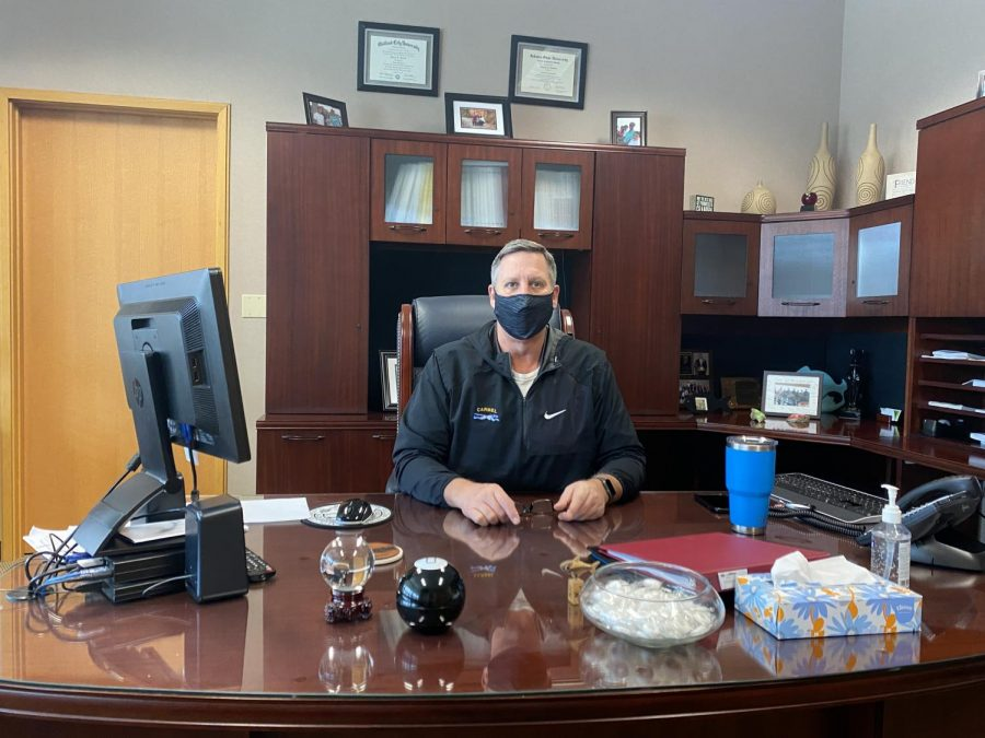 Principal Tom Harmas sits at his desk, wearing a mask to comply with COVID-19 guidelines. He said administration is currently planning for next year by analyzing staffing needs and determining which changes from the current school year, such as staggered bells and mandated lanyards, will remain in future years.