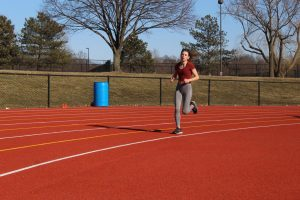 WARMING UP:  Lily Rose, varsity women's track and field team member and junior, runs a lap as a part of her  warmup. Rose said she thinks cross country has developed a supportive culture to help any girls who may be struggling with body image issues.
