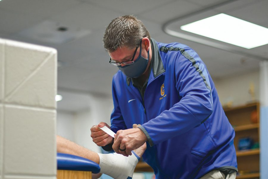 Athletic+trainer+Chad+Bergman+helps+to+adhere+tape+on+an+athlete+to+help+prevent+future+injuries.+Bergman+said%2C+Bergman+said+he+likes+his+job+as+an+athletic+trainer+primarily+because+it+allows+him+to+dwell+on+his+love+of+both+sports+and+helping+others.+