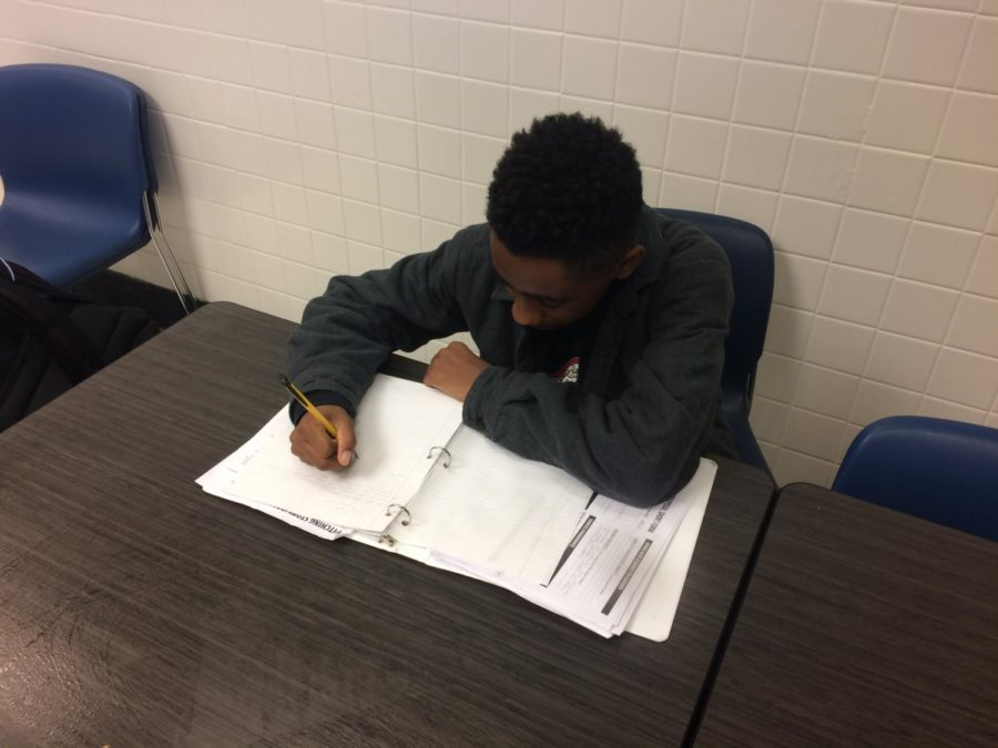 Senior Myles Embry works on his homework during his lunch period. Embry says he often sees maintenance workers working around the school when walking from lunch to his classes.