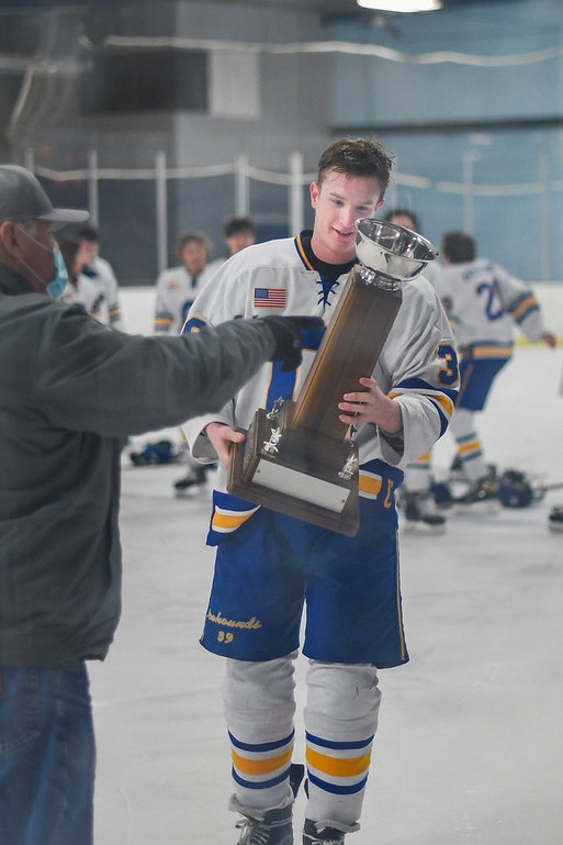 """Micah Hartsock, Icehounds gold team member and senior, holds the Hoosier League Tournament trophy after defeating Hamilton Southeastern's team 5-2 on Feb. 21. """"Everyone is doing their part,"""" Hartsock said. """"This win was a great stepping stone going into the state tournament."""""""