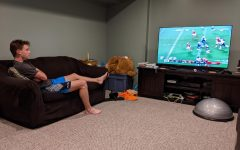 Sophomore Neil Fairman watches a NFL game between the Kansas City Chiefs and the Houston Texans on his TV. Fairman said he supports stadiums being filled to at least half capacity because it would improve the atmosphere at games.  (NEIL FAIRMAN SUBMITTED PHOTO)