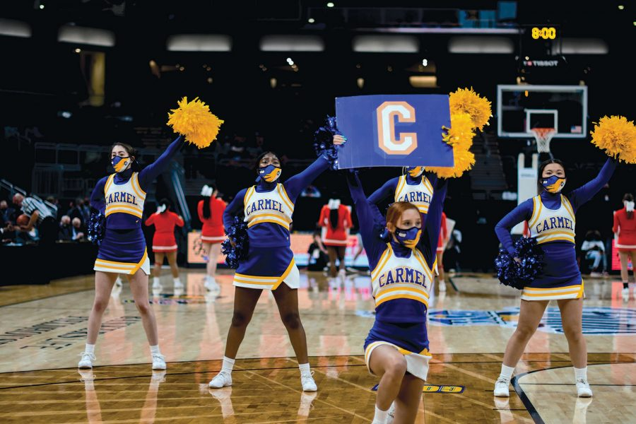 Trinity Griffin, varsity cheerleader and senior, poses during a cheer motion with some of the other cheerleaders. She said cheerleading has helped her immensly through high school due to the fun and collective atmosphere it brought to her.