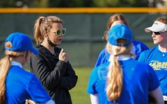 Ginger Britton, head coach of the CHS softball team, talks strategy with players during a game. Britton said female-to-female communication with coaches encourages players to talk about their struggles.