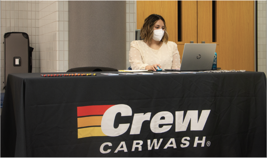 A representative for Mike's Crew Carwash waits for students to arrive at her station at the job fair. The job fair was an opportunity for students to find and gain work experience while still in high school.