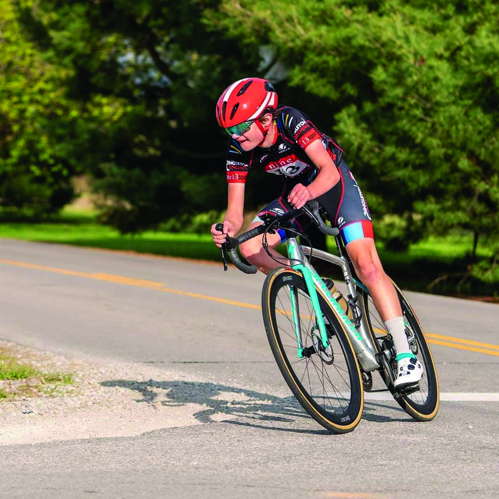 Griffin Raduchel, competitive cyclist and junior, goes down a road on his road bike. Raduchel said competitive cycling has taught him to push himself further.