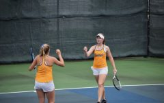 FIST BUMP: Senior Leila Antony (right) celebrates with one of her teammates during a tennis match. Antony and several others from Carmel qualified for the national tennis tournament run by the USTA (United States Tennis Association). She said working with a team has taught her how to build friendships and learn life skills.