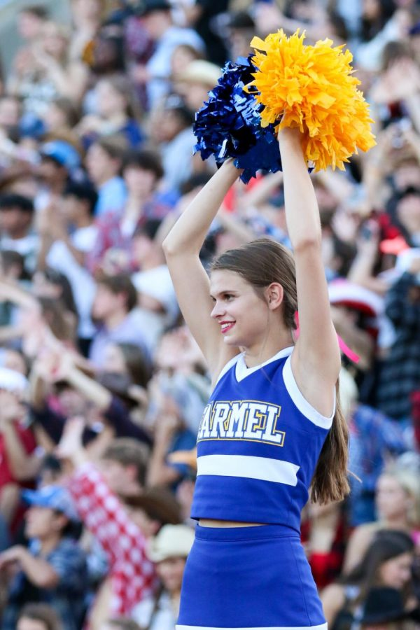 FLYING HIGH: Kindle Hohlt, varsity fall cheerleader and senior, preforms a stunt during a football game on Sept. 17. Before the start of the game, Hohlt participated in a senior night recognition with her parents and fellow seniors.