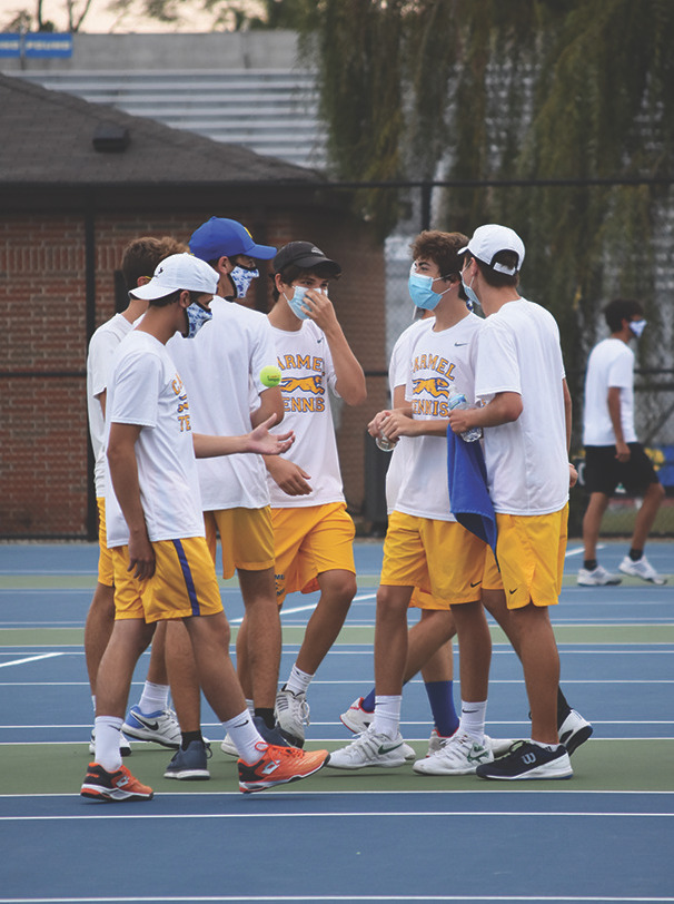 Ethan Katz (center), tennis player and senior, talks to his teammates on the court. According to Katz, although the tennis team does not have captains, he looks forward to mentoring his younger teammates and lead the team well.