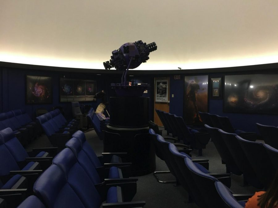 The GOTO star machine stands in the middle of the planetarium, centered underneath the dome. Viewers will sit at these blue seats during the show.
