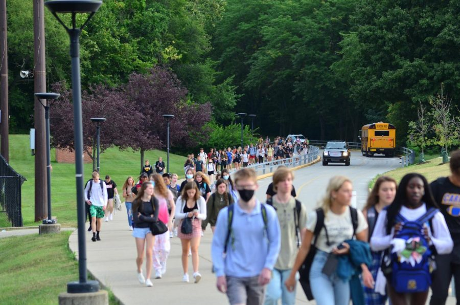 Students walk up the trail towards school after parking their cars as a bus leaves the campus in the background. Recent bus driver shortages have forced some students to carpool or drive to school.