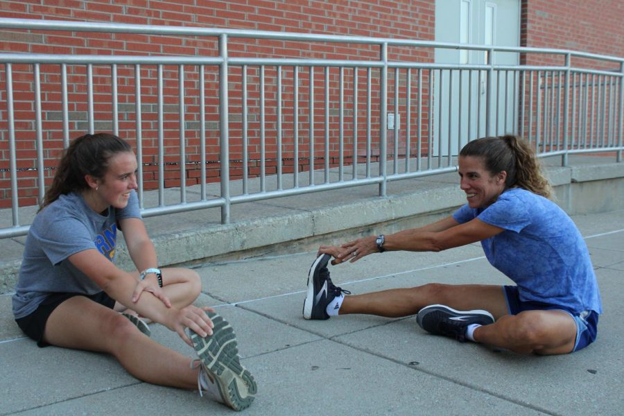 Junior Jacqueline Roth (left) and her mom, Laura Roth (right), sit down to stretch together before going on a run. Mrs. Roth said that working out together is a bonding experience because she communicates with her family while exercising and gets to learn more about them.