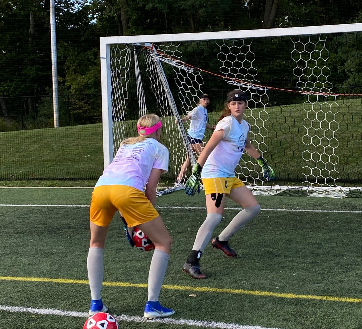Goalkeeper and junior Bethany Ducat (right) prepares to save a ball about to be thrown by goalkeeper and junior Aubree Empie while warming up for a game against Warren Central on Sept. 15