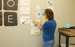 Green Action Club sponsor and CCS Green Team representative Carey Anderson hangs a poster for the club on her wall. Anderson said she helps students increase awareness of environmental issues.