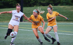Kathryn Hartung (center), defensive center midfielder and junior, defends against an opposing player in a game against Guerin Catholic on Aug. 20. Hartung said she frequently works on communication with fellow defensive players on the team to make sure the team concedes very few goals.
