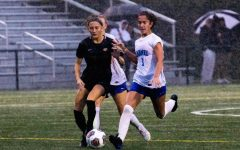 Luci Bair, varsity women's soccer player and senior, dribbles the ball in a Sectional game against Guerin. Bair said facing higher ranked teams drives the team to play harder.