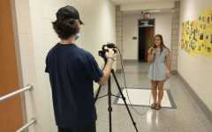 Anchor and senior Morgan Mace begins recording a video with senior Kayden Lyons. The video was a collection of student interviews on their favorite halloween traditions.