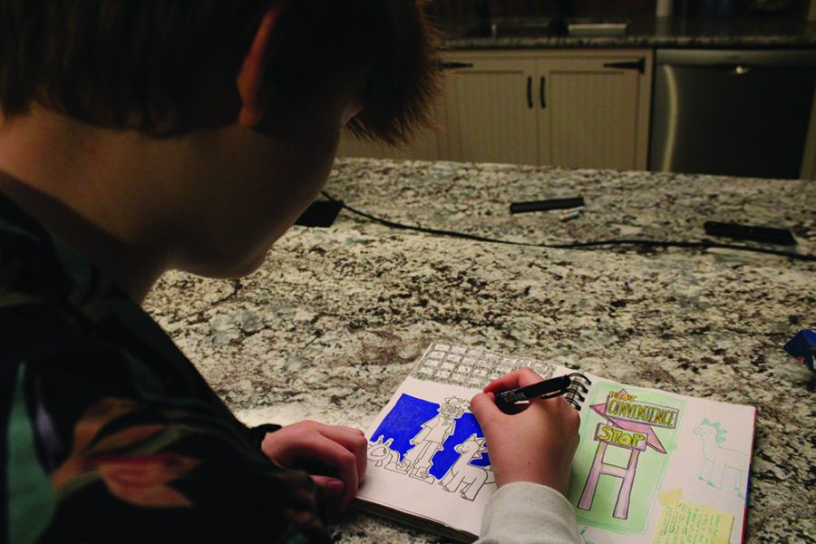 sketchin' it out: Sophomore Ren Olson works on character designs for a project in his sketchbook. He said he hopes to send it in as part of a portfolio for admission in pre-college programs, and said he is considering a career for animation.