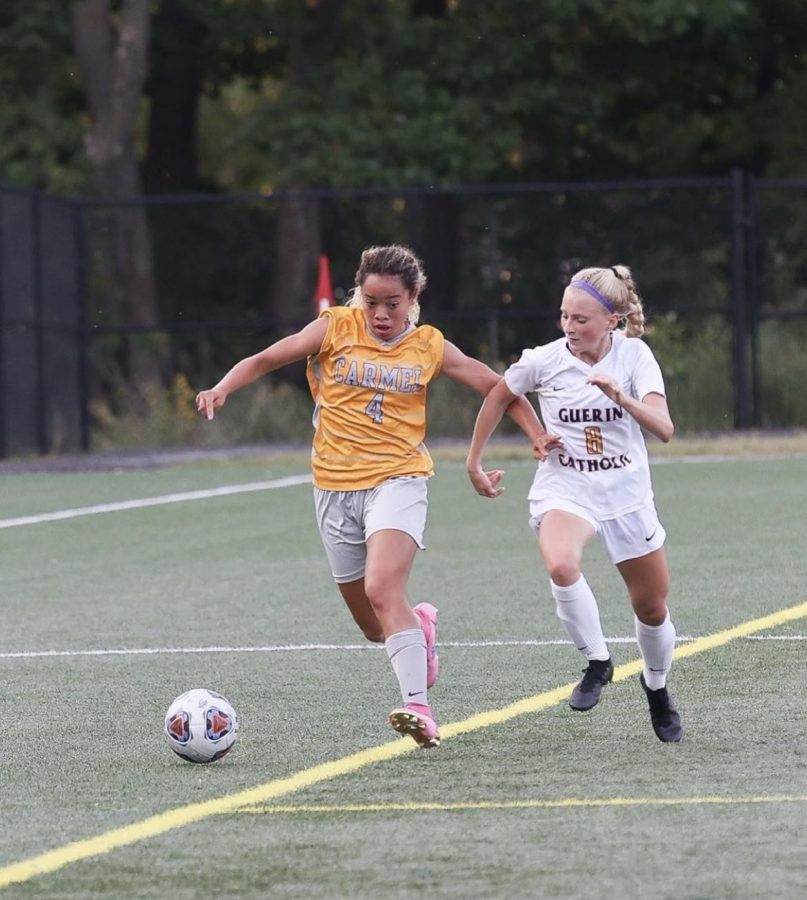 Saliyah Brady (left), captain and senior, dribbles the ball during a game against Guerin Catholic on Aug. 20. Brady said she believes the team is capable of making it to the State Finals and it will need to continue to play as a team to do so.