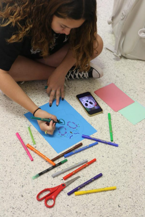 Freshman Regina Hyde draws a paper skull decoration for Día de los Muertos. Hyde said one of her favorite parts of the celebration was getting to eat decorated sugar skulls and other sugary desserts. Hyde said Día de los Muertos is a holiday that can help reduce the fear of death.