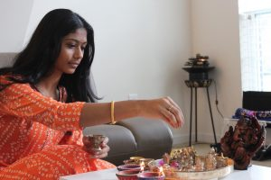 """Sophomore Roohi Sanka sprinkles akshinthalu, a mix of tumeric and rice, onto figures of gods. """"There was a Hindu god in human form who came back to his town after years of penance and another god defeated a demon-like figure who was terrorizing the area. Those (stories) are told on Diwali,"""" she said."""