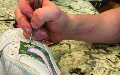 artful strokes:  Senior Nash Cheslock adds details to a pair of white Nike Air Force 1 shoes. Cheslock said he mostly uses acrylic paints for these projects.