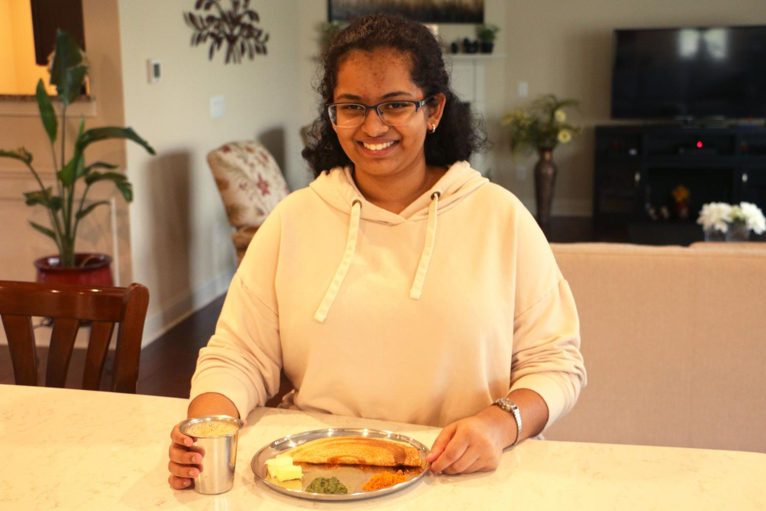 Senior Sneha Srivasta poses with traditional Indian food from her culture. She says that although she has adapted to the differences in culture in the United States, her family still eats traditional food like dosa which is an Indian bread that has been incorporated as the United States diversifies its culture.