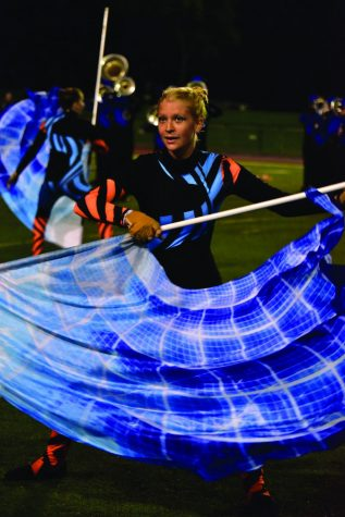 Sophomore Lorelai Sokol performs during halftime of the Carmel football game against Warren Central on Oct. 8. Sokol is a member of the Carmel Color Guard and is beginning the Winter Guard season in November. The color guard performs alongside the marching band at football games and competitions.